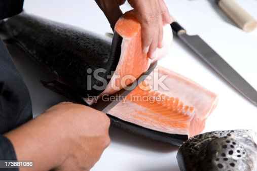 A Japanese Sushi Chef Cutting Raw Fish For Sushi.
