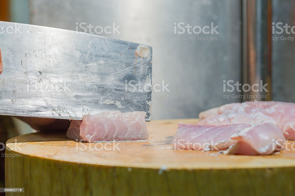 cutting fishes with knife stock photo
