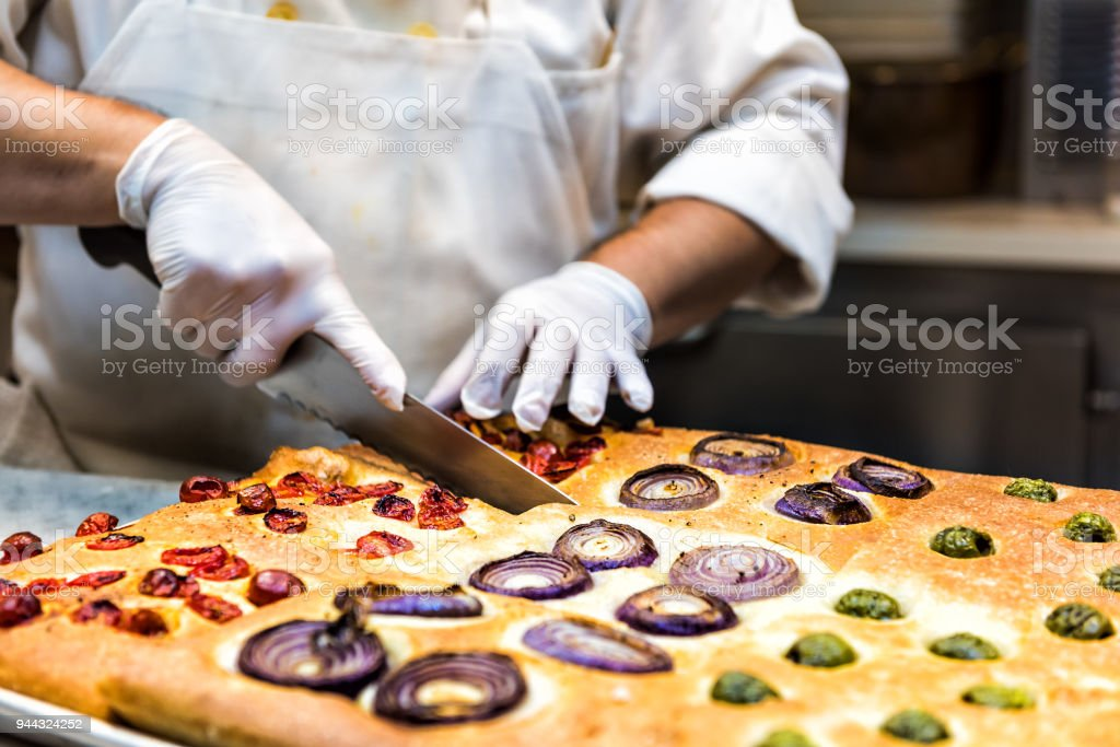 Cutting foccacia bread with knife, toppings baked in oven, chef in restaurant kitchen with sanitary hygiene gloves stock photo
