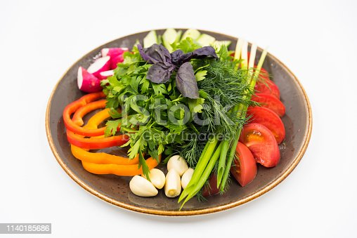 Cutting fresh vegetables on the white plate on white background. Photo.