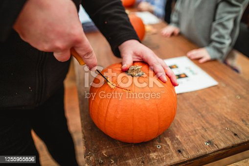 Unrecognisable person carving pumpkins at a farm after picking them in preparation for Halloween. They are cutting into the top of the pumkpkin.