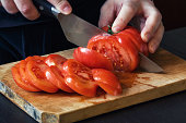 Close-up view of fresh and ripe red extra large sliced tomato on wooden cutting board