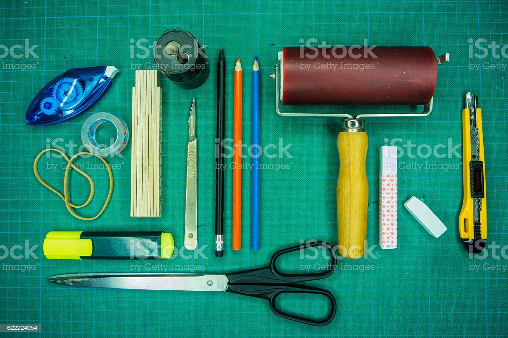 Cutting mat with various stationary tools, knolling, shot from a stock photo