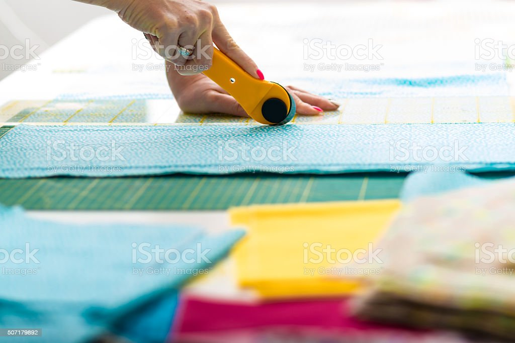 Cutting material with rotary blade cutter for quilt stock photo
