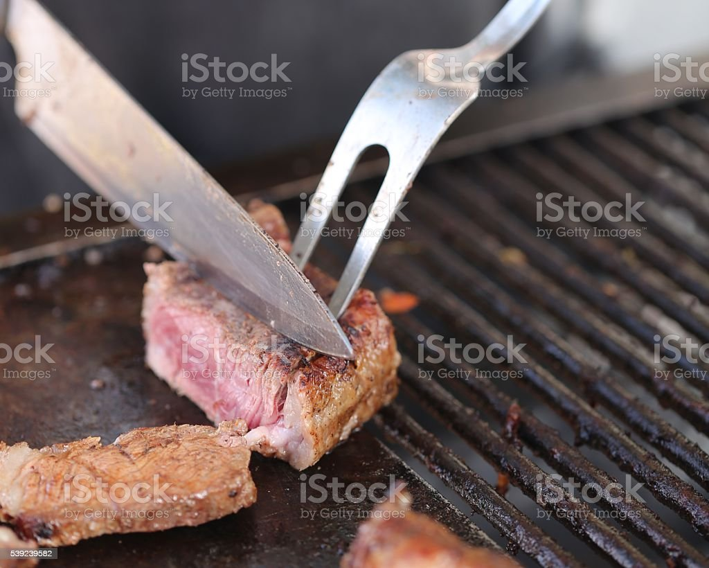 Cutting Meat With GrillTools royalty-free stock photo