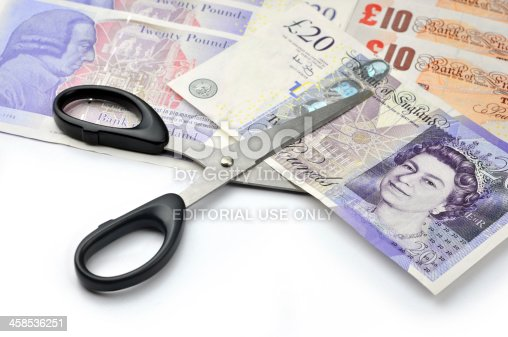 London, United Kingdom, July, 09 2011:  Studio shot of scissors cutting twenty pounds British bank note, with twenty and ten pounds bank notes in the background.