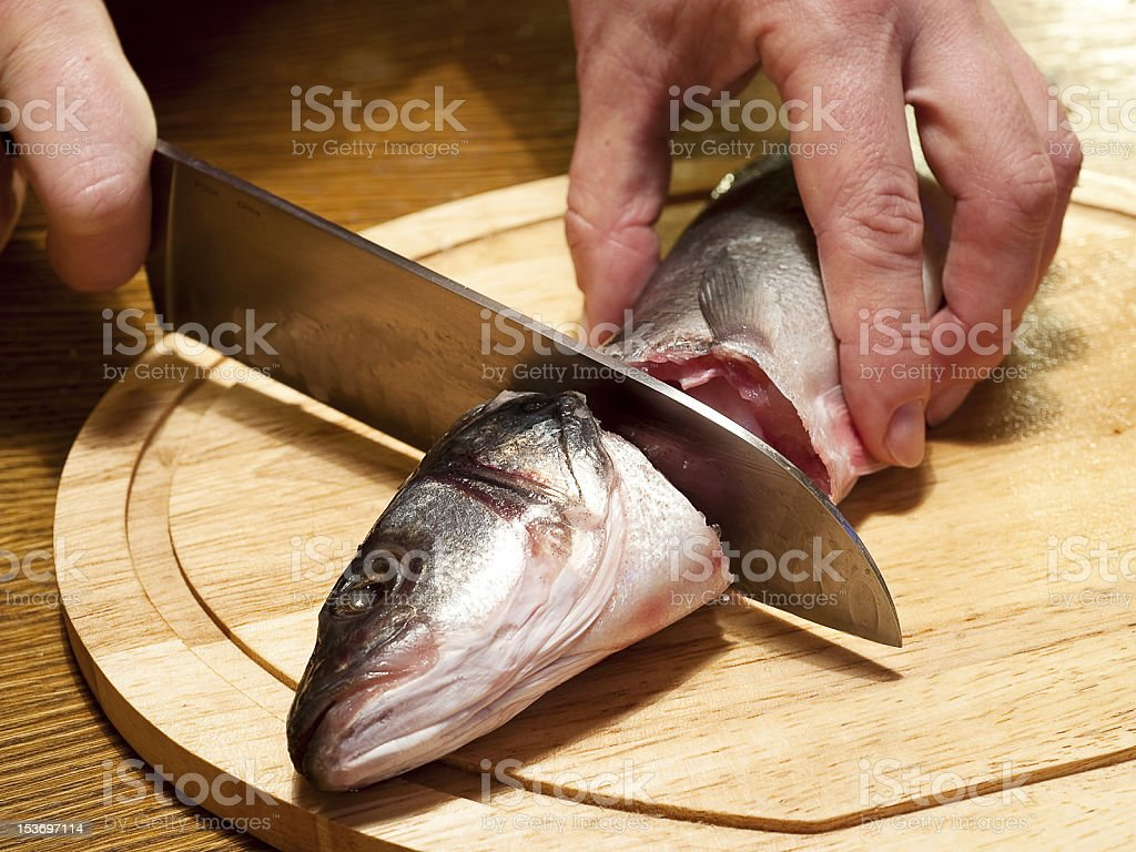 Cutting of crude fish by a knife stock photo