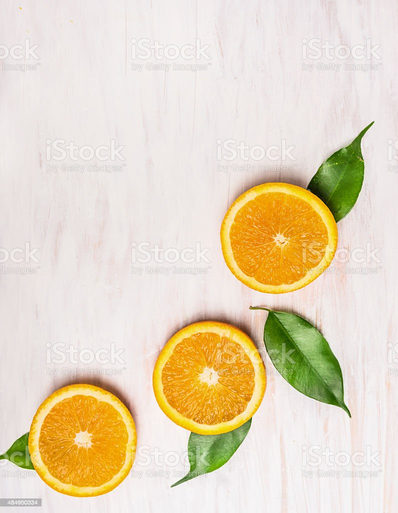 cutting orange fruits with leaves on white wooden background stock photo