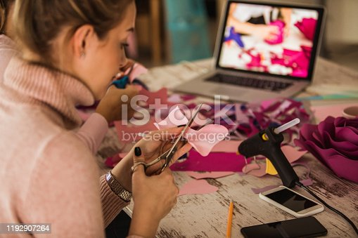 Selective focus of young woman sitting at the table and following step by step tutorial on how to make decorative paper flowers. She is cutting out flower petals with scissors and later using hot glue gun to glue them together.
