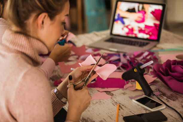Cutting out flower petals while crafting decorative paper flowers stock photo