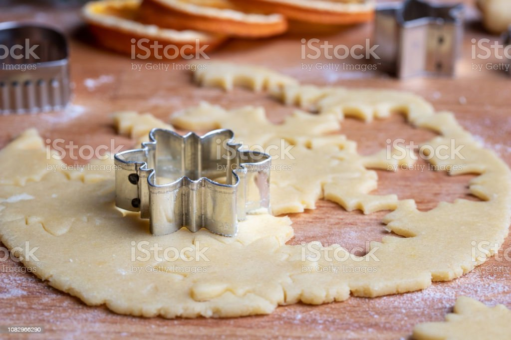 Cutting out star shapes from rolled out dough to prepare traditional...