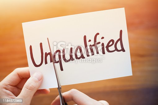 Cutting Out the Word Unqualified and Qualified on Paper with Scissors.