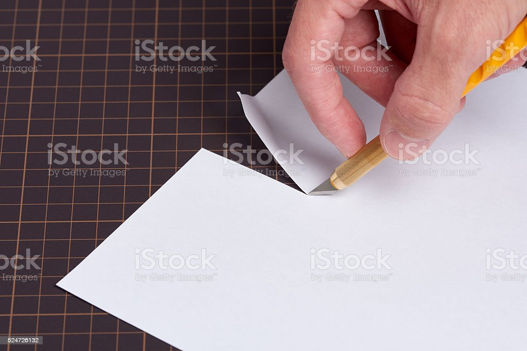 Cutting Paper with Utility Knife stock photo