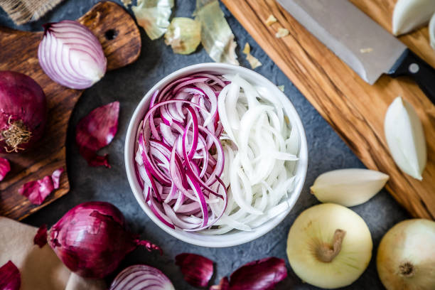 Cutting red and golden onions Top view of a bowl full of red and golden sliced onions surrounded by a wooden cutting board with a kitchen knife on top and whole and sliced golden and red onions. The bowl is at the center of the image. Low key DSLR photo taken with Canon EOS 6D Mark II and Canon EF 24-105 mm f/4L spanish onion stock pictures, royalty-free photos & images
