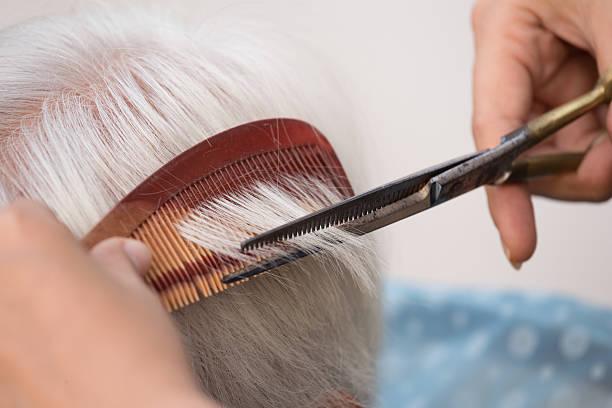cutting senior woman's gray hair – Foto