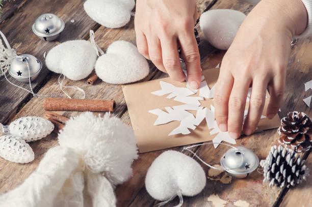 schneiden schneeflocke für weihnachts-dekor - basteln mit kindern weihnachten stock-fotos und bilder