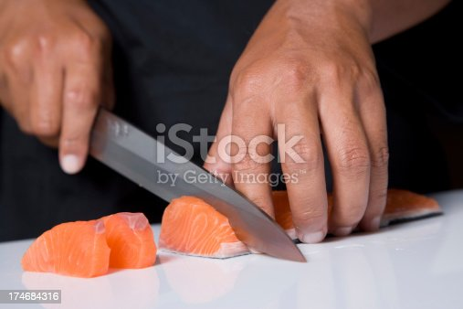A Japanese Chef Cutting Raw Fish For Sushi.