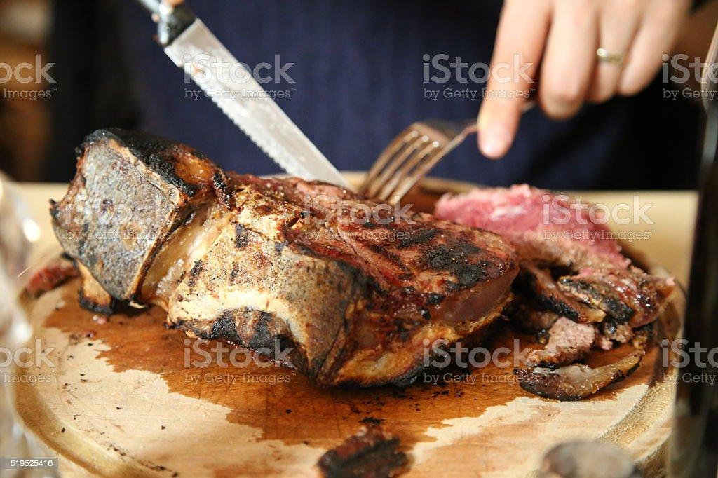 Cutting T-born steak stock photo