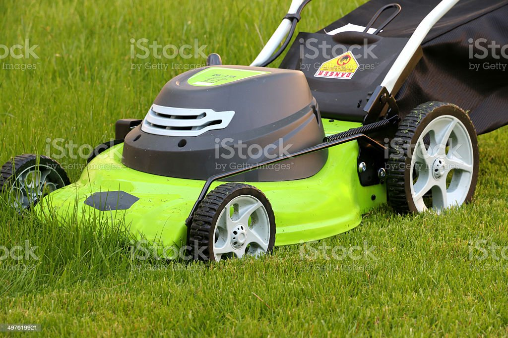 Cutting the grass with lawn mower stock photo