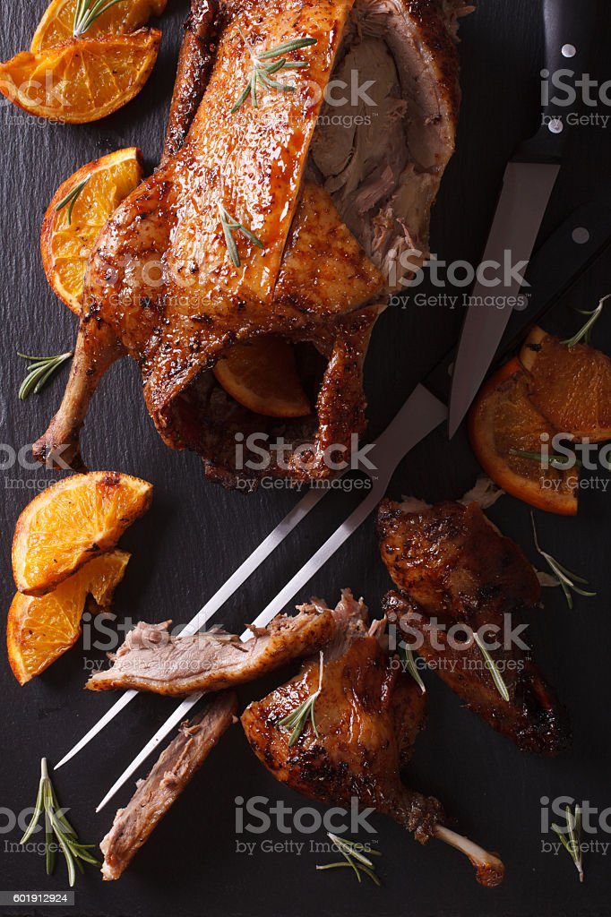 Cutting the roast duck and oranges closeup. vertical top view stock photo