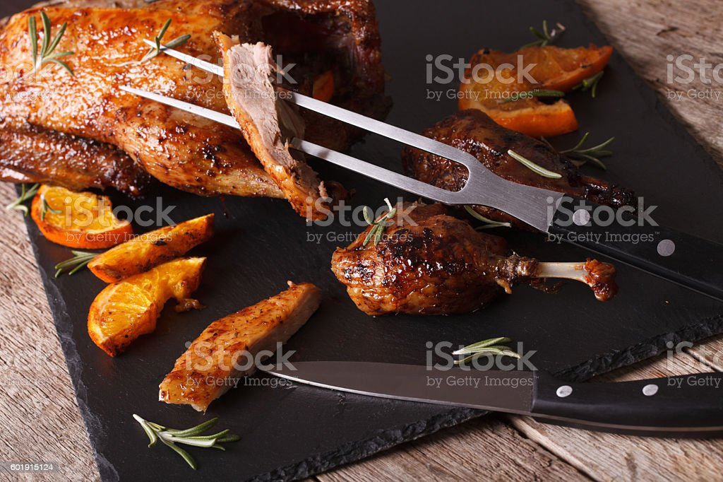 Cutting the roast duck close up on a slate board stock photo