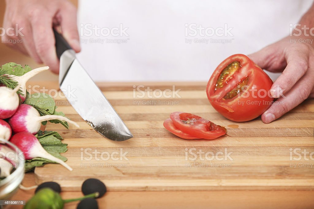Cutting tomato. chef's hands chopping tomatoes with knife royalty-free stock photo