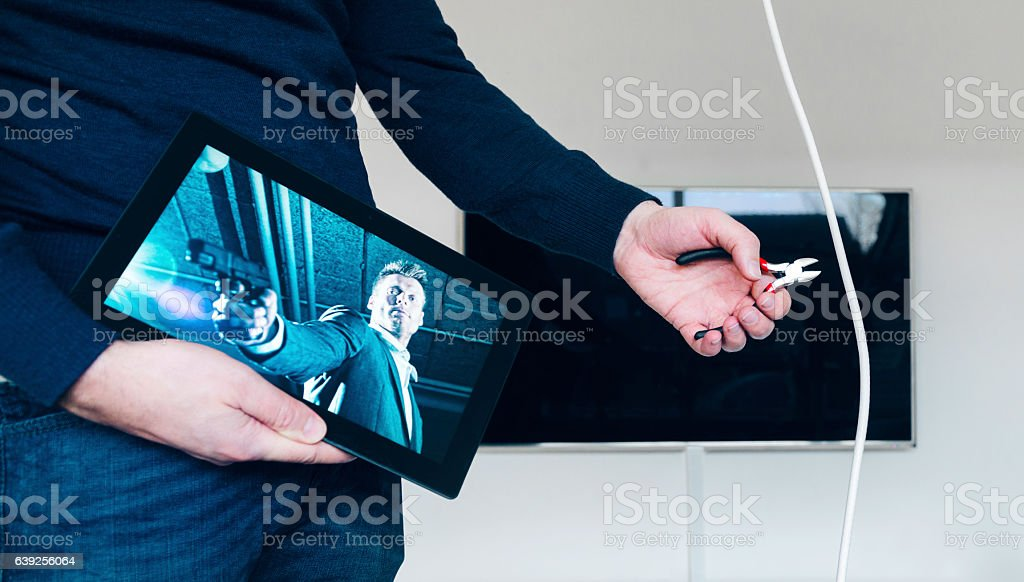 Cutting tv cable and switching to streaming movie on tablet stock photo