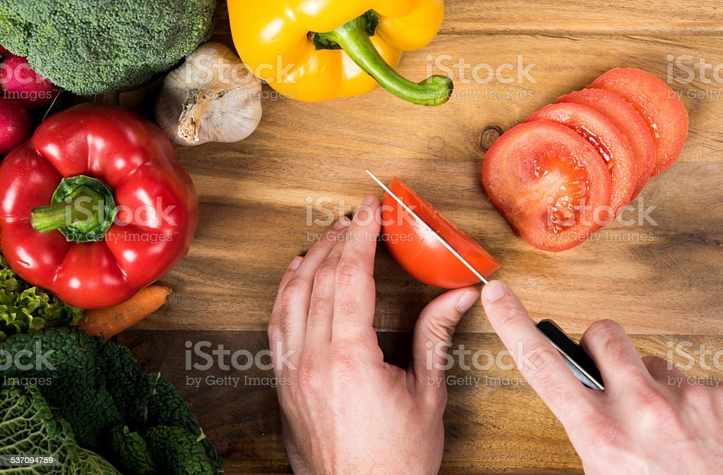 Cutting vegetables on wooden board stock photo