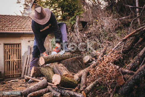 Young man preparing wood logs for winter using electric chainsaw.