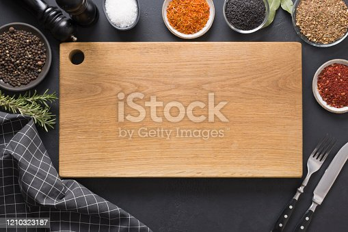 Cutting wooden board with spices and ingredients for cooking and marinade tasty dishes on black. Space for text. View from above.