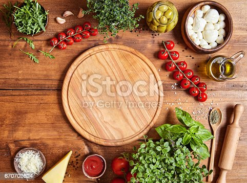 istock Cutting wooden board with traditional pizza preparation ingridients: mozzarella, tomatoes sauce, basil, olive oil, cheese, spices. 670702624