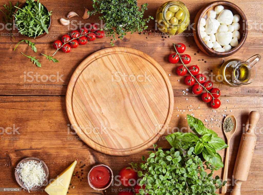 Cutting wooden board with traditional pizza preparation ingridients: mozzarella, tomatoes sauce, basil, olive oil, cheese, spices. stock photo