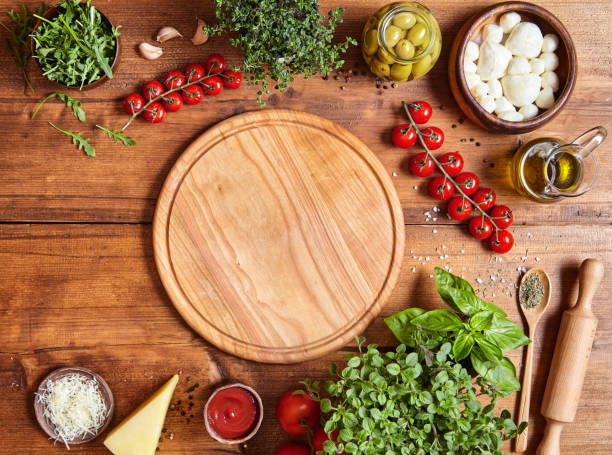 cutting wooden board with traditional pizza preparation ingridients: mozzarella, tomatoes sauce, basil, olive oil, cheese, spices. - savory food stock photos and pictures