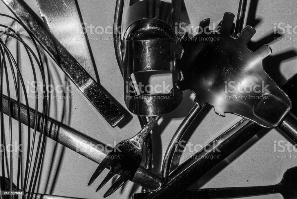 cuttlery, knives, forks, spoons and assorted kitchen utensils abstract black and white stock photo