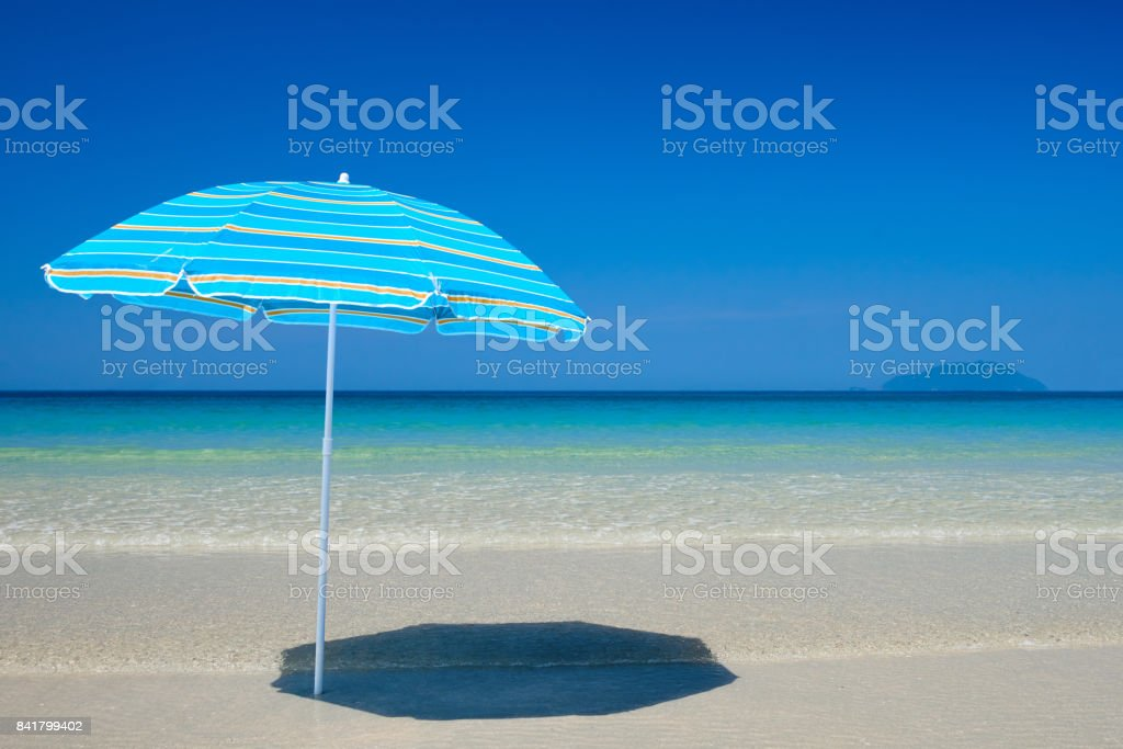 Cyan beach umbrella on the tropical beach stock photo