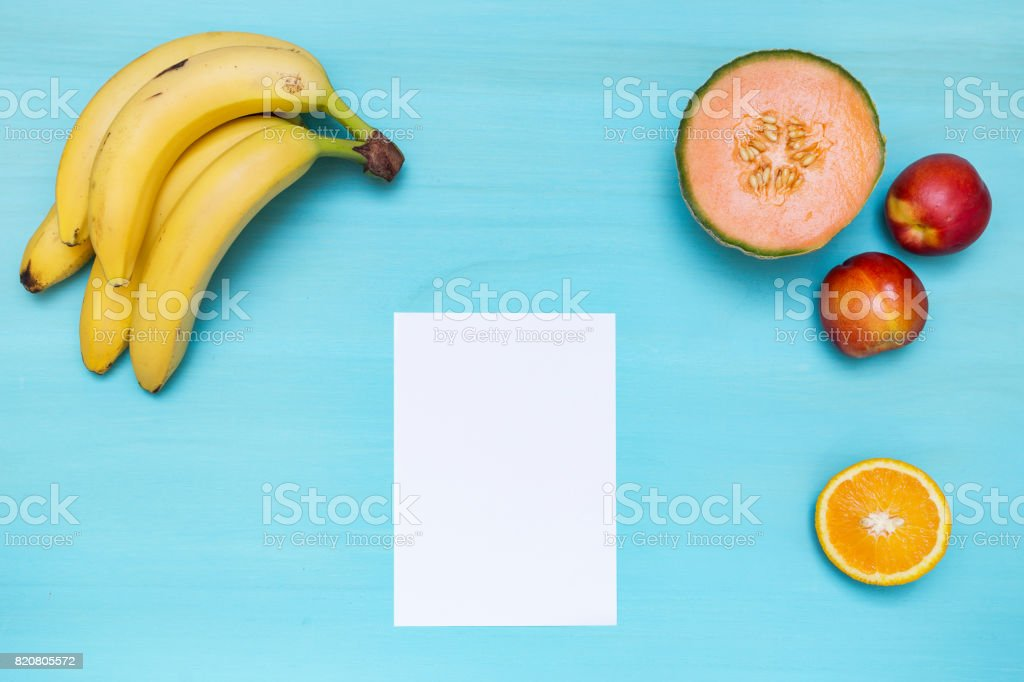 Cyan tabletop with fruit and a white paper stock photo
