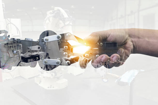 Cyber communication and robotic concepts. Industrial 4.0 Cyber Physical Systems concept. Double exposure of Robot and Engineer human holding hand with handshake and automate robot arm background. stock photo
