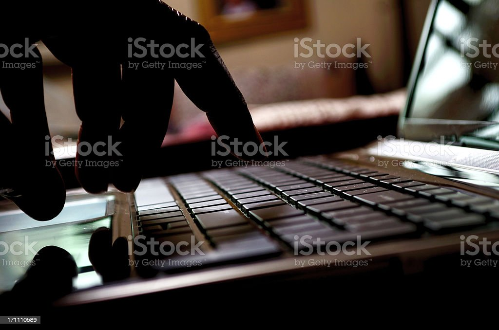 cyber crime hacker typing on laptop stock photo