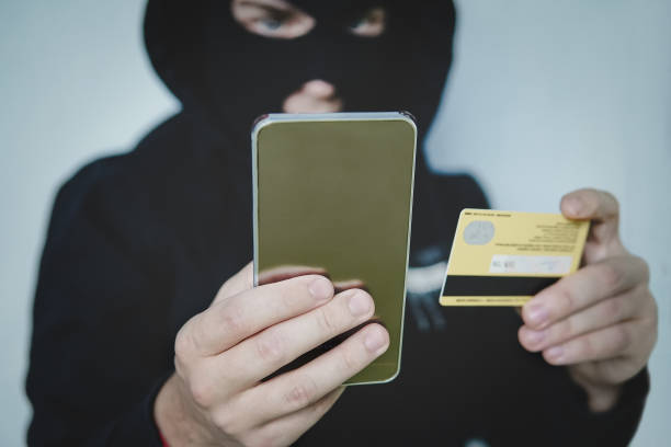 Cyber criminal in balaclava enters the information of a personal bank account. Credit card fraudulent scheme. Stealing cyber money using mobile. New ways of fraudulent transactions via online banking stock photo