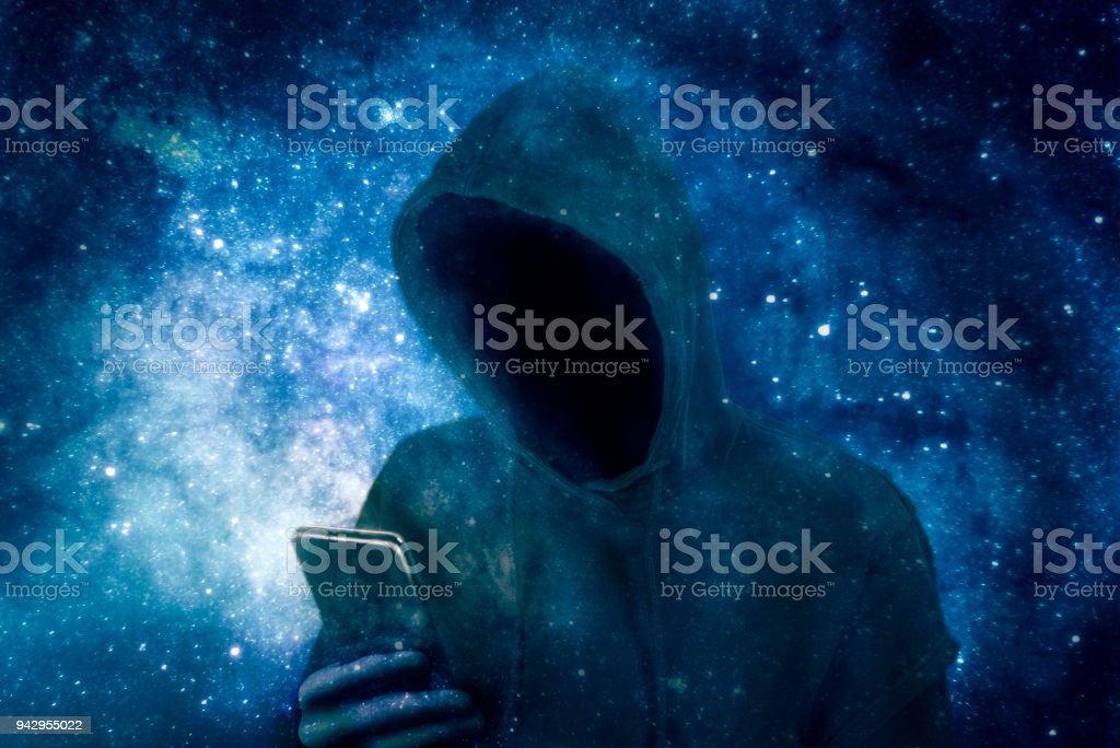 Cyber criminal in hoodie with smartphone stock photo