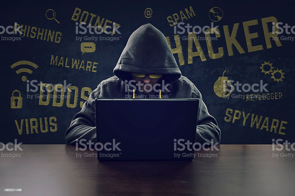 Cyber criminal stealing secrets with laptop stock photo