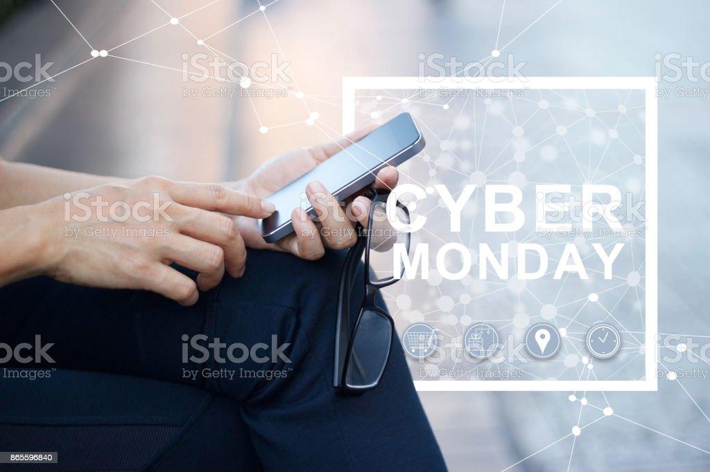 Cyber Monday, homme à l'aide de smartphone en mains et connexion réseau icône sur fond extérieur pastel - Photo