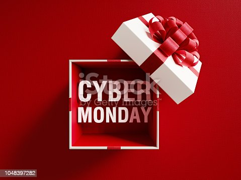 Cyber Monday text is coming out of a white gift box tied with red ribbon on red background. Horizontal composition with copy space. Directly above. Great use for Christmas and Valentine's Day related gift concepts.