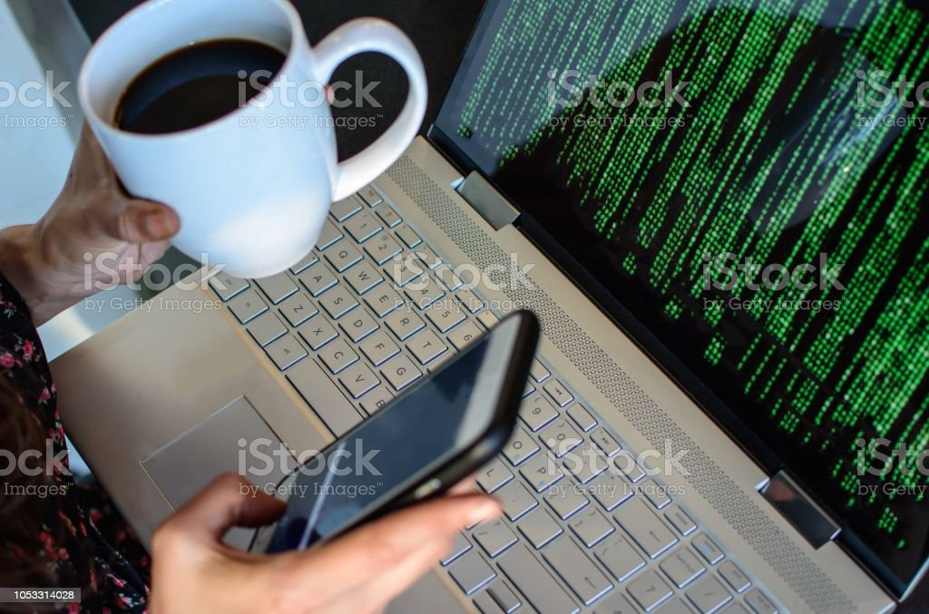 Cyber risk and cyber security woman with laptop and cell phone calling for help stock photo