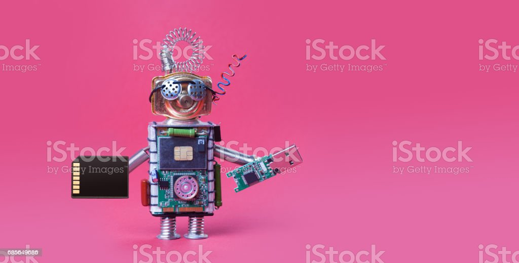 Cyber safety data storage concept. System administrator robot toy with usb flash stick and memory card on red background. Copy space macro view photo stock photo