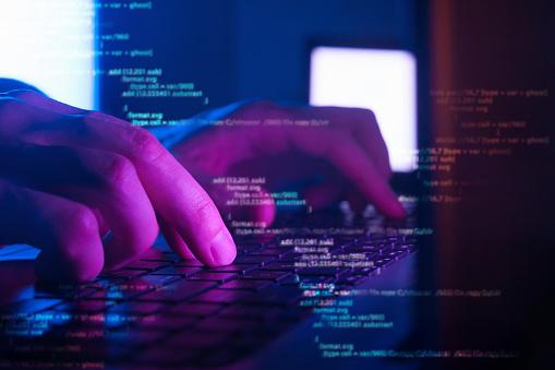 programmer or hacker coding on laptop in dark room