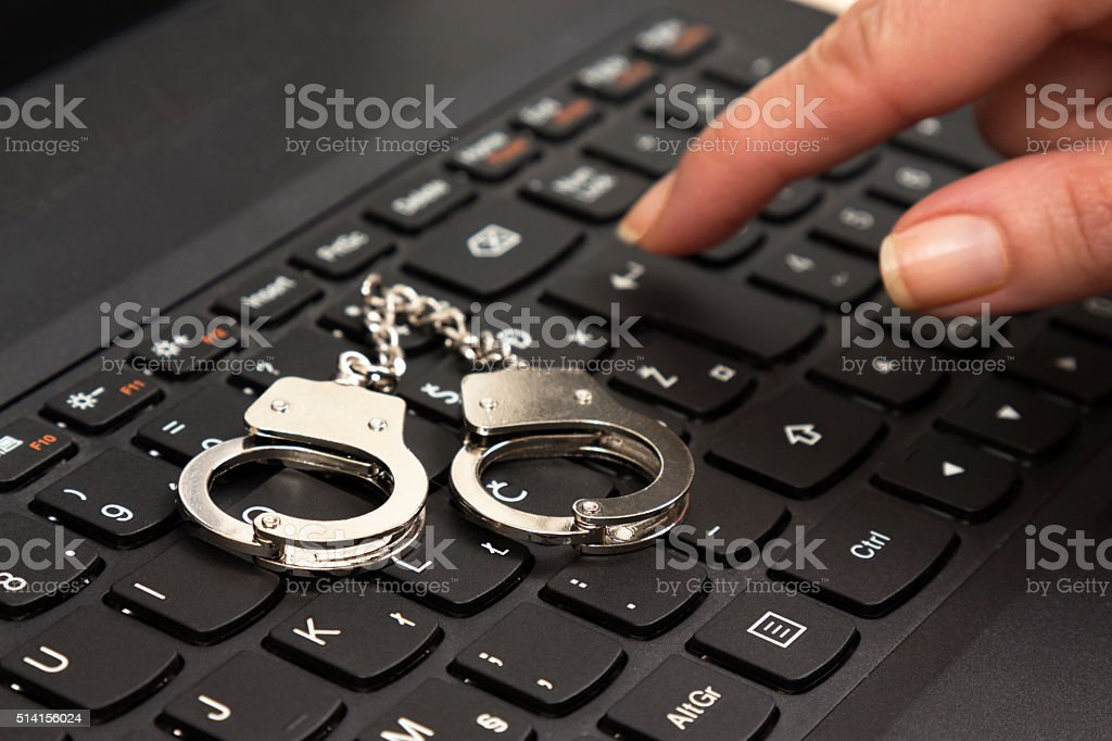 Cybercrime concept with small handcuffs on computer keyboard stock photo