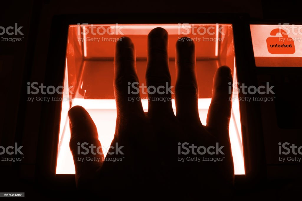 cybersecurity concept - person unlocks a computer on a divice with his fingerprints stock photo