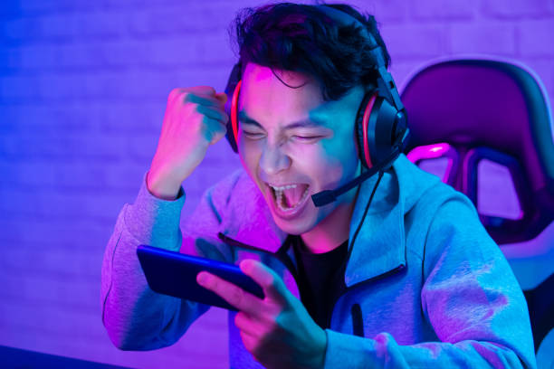 cybersport gamer win the game cybersport gamer win the game and cheer with fist gesture leisure games stock pictures, royalty-free photos & images
