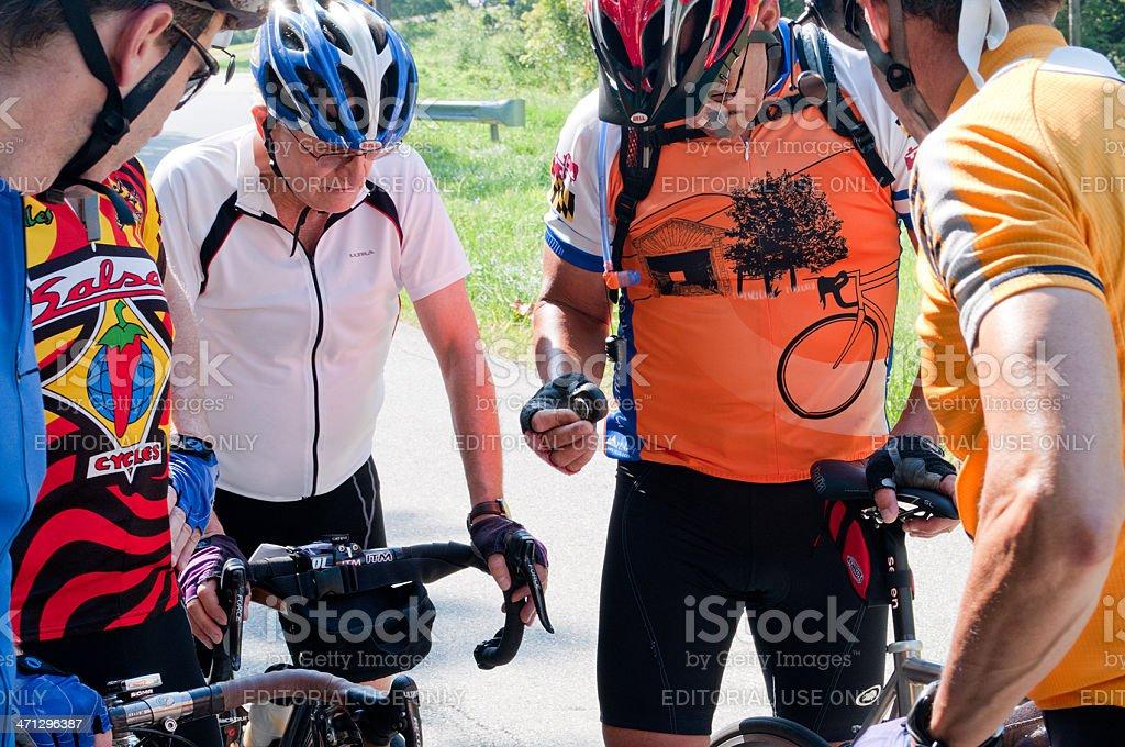Cycists Stop to Assess and Fix a Damaged Bike stock photo